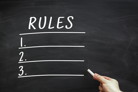 govern: Rules List written on the blackboard with hand holding white chalk aside. Stock Photo