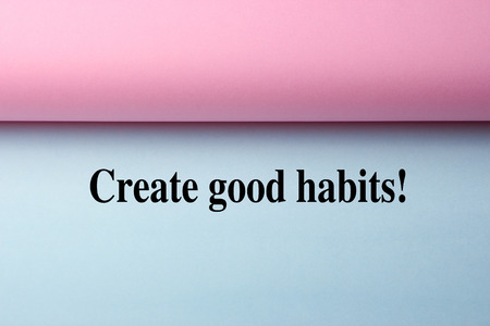 good habits: Black text Create Good Habits on the blue paper with pink paper aside. Stock Photo
