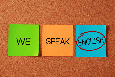 english text: We Speak English text written on sticky notes pasted on corkboard.
