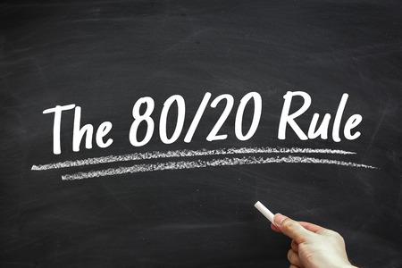 Tekst De 80 20 Rule geschreven op het bord met de hand houden wit krijt opzij. Stockfoto