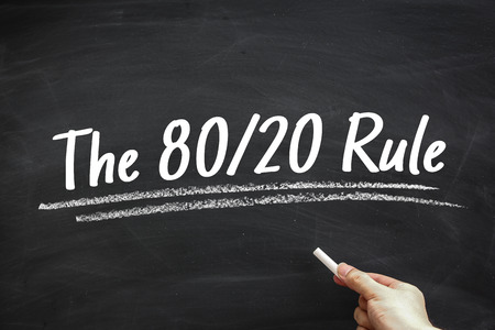 Text The 80 20 Rule written on the blackboard with hand holding white chalk aside.