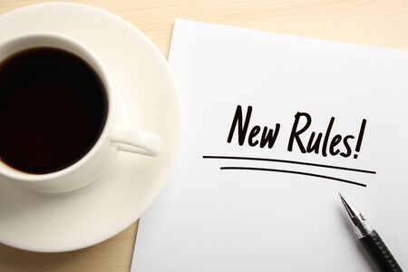 new rules: Text New Rules written on the white paper with coffee aside. Stock Photo