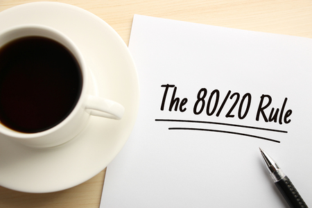 Text The 80 20 Rule written on the white paper with coffee aside.
