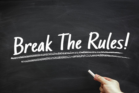 breaking the rules: Text Break The Rules written on the blackboard with hand holding white chalk aside. Stock Photo