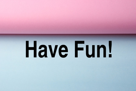 have fun: Black text Have Fun on the blue paper with pink paper aside. Stock Photo