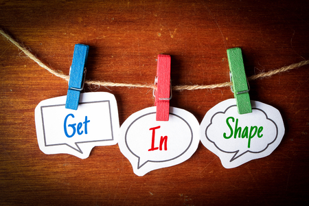 get in shape: Paper speech bubbles with text Get In Shape hanging on the line against dark wooden background.