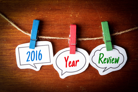 Paper speech bubbles with text 2016 Year Review hanging on the line against dark wooden background.