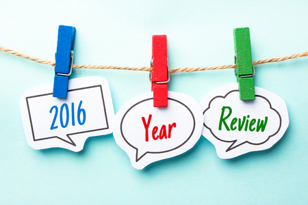 Paper speech bubbles with text 2016 Year Review hanging on the line. Stock Photo