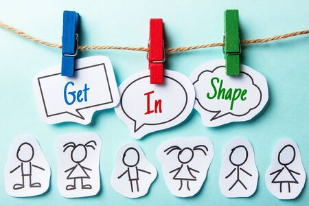 get in shape: Paper speech bubbles with text Get In Shape hanging on the line with some paper people under. Stock Photo