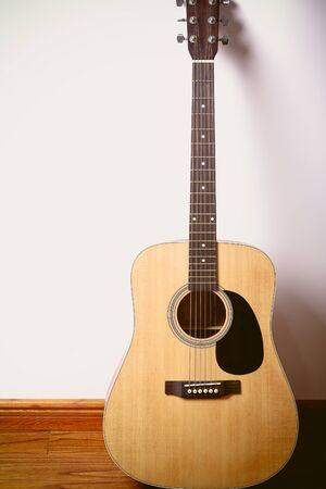 acoustical: Acoustic guitar standing against white wall background.