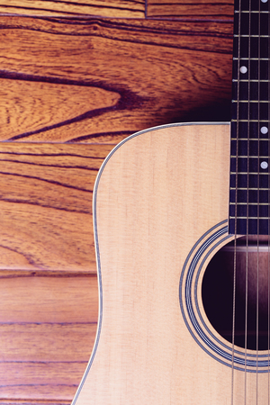 bluegrass: Closeup shot of acoustic guitar on wood background.
