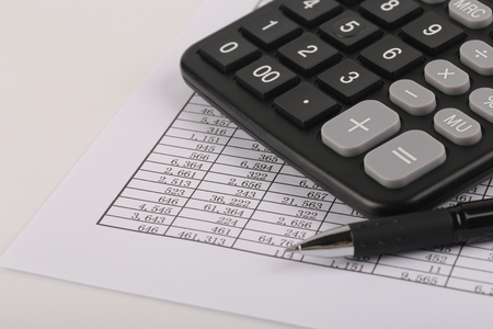 examiner: A calculator and a ball pen is on a balance sheet. Concept for sales, profit and cost.