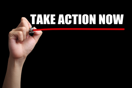 take action: Hand is drawing a red line under the text Take Action Now with black background. Stock Photo