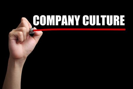 La mano está drenando una línea roja bajo el texto de Cultura de la empresa con el fondo negro. Foto de archivo