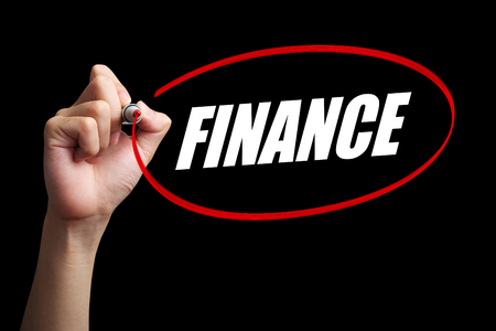interst: Hand is drawing a red circle around the word Finance with black background.