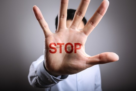 layoffs: Man open the hand with the text Stop. Stock Photo