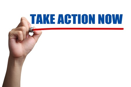 take action: Hand is drawing a red line under the text Take Action Now on the transparent whiteboard. Stock Photo