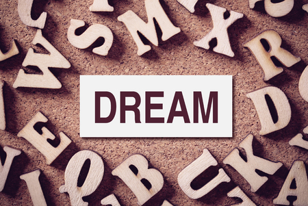 endearment: Corkboard covered with word Dream and multiple wooden letters. Stock Photo