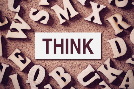 cogitate: Corkboard covered with word Think and multiple wooden letters.