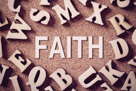 spiritualist: Corkboard covered with word Faith and multiple wooden letters. Stock Photo