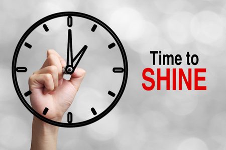 time to shine: Hand is drawing a clock with text Time To Shine Concept aside with blurred gray background.