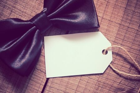 Black bow tie with blank tag aside for fathers day background. With copy space.