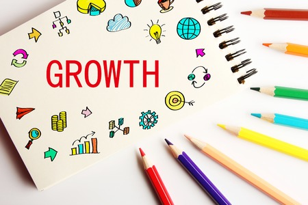 aside: Growth business concept on the note with some colorful pencils aside.