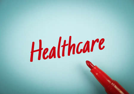 mark pen: Text Healthcare written on blue paper with red mark pen aside. Stock Photo