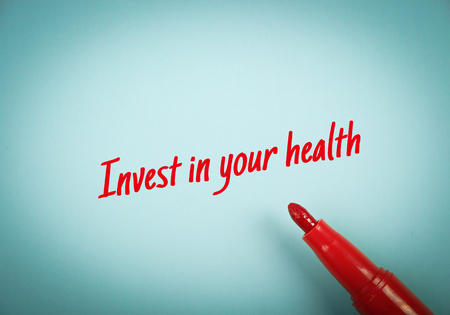 mark pen: Text Invest In Your Health written on blue paper with red mark pen aside. Stock Photo