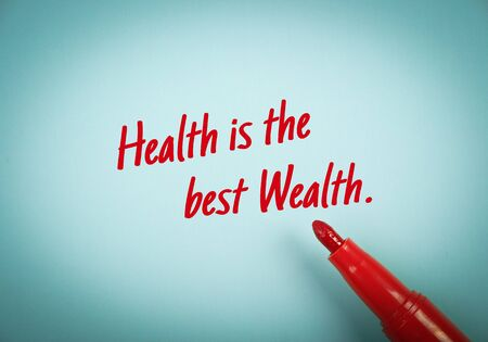 mark pen: Text Health is the Best Wealth written on blue paper with red mark pen aside.