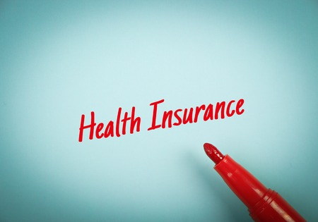 mark pen: Text Health Insurance written on blue paper with red mark pen aside.