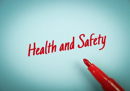 occupational risk: Text Health and Safety written on blue paper with red mark pen aside. Stock Photo