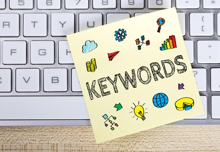 Keywords business concept on the sticky note pasted on the keyboard.