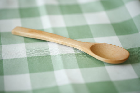 food supply: Wooden spoon is lying on the cloth background.