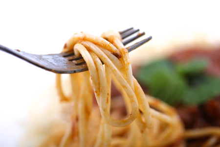 Close up view of a fork scooping spaghetti