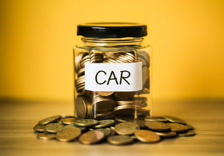 A lot coins in glass money jar with yellow background. Saving for car concept. Foto de archivo