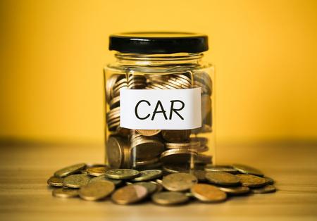 Wiele monet w szklanym słoiku z żółtym tłem. Oszczędność na koncepcję samochodu. Zdjęcie Seryjne