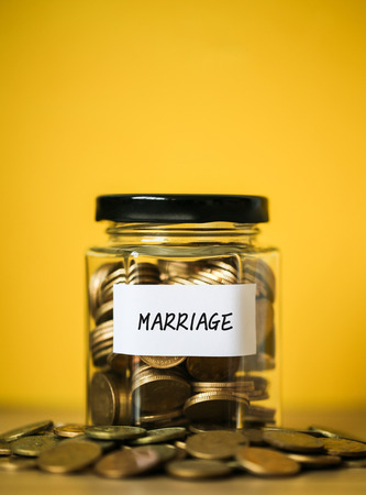A lot coins in glass money jar with yellow background. Saving for marriage concept.