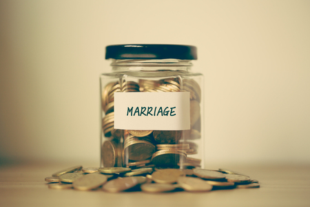 A lot coins in glass money jar on the table. Saving for marriage concept.