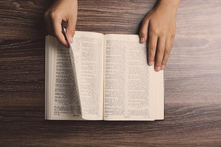 Handen met geopende Heilige Bijbel op het houten bureau.
