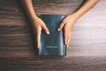 Handen met heilige bijbel op het houten bureau.