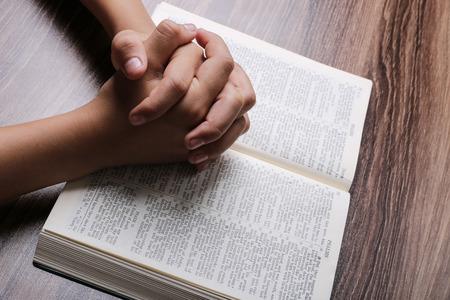 Biddende handen met geopende heilige bijbel op het houten bureau. Stockfoto