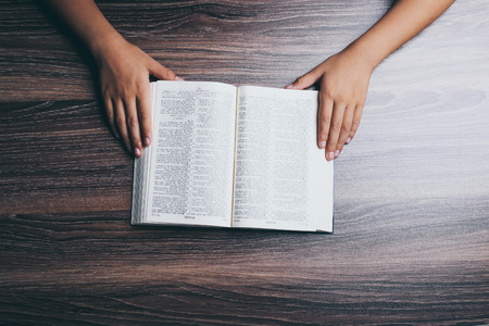 Hands with opened holy bible on the wooden desk.
