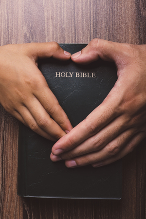 Holy bible with heart shape hands on the wooden desk.
