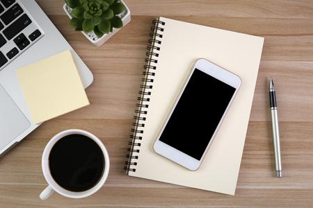 Mesa de escritorio de oficina de madera con laptop, taza de café y suministros.