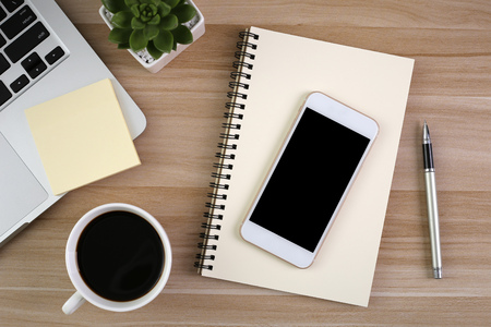 Table de bureau en bois avec ordinateur portable, tasse de café et fournitures.