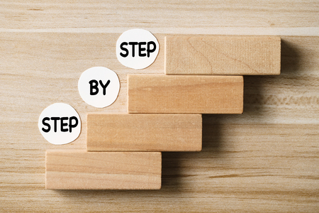 Step by step concept on the wooden desk background.