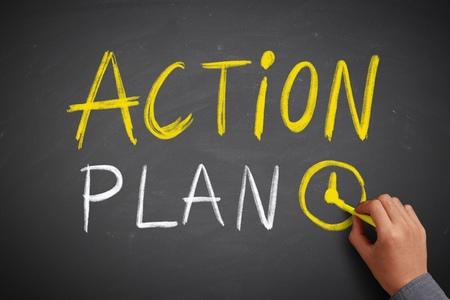 Hand schreibt Aktionsplan an die Tafel