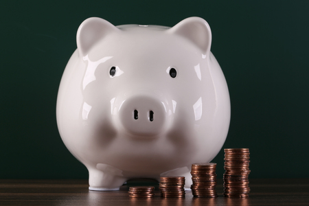 Piggy bank with growth coins against black background