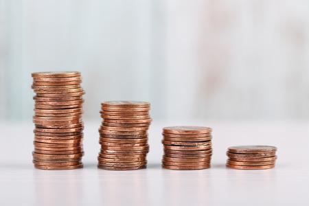 Pile di monete in un concetto finanziario di diminuzione.